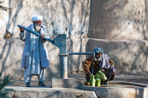 Afghan men collect the water