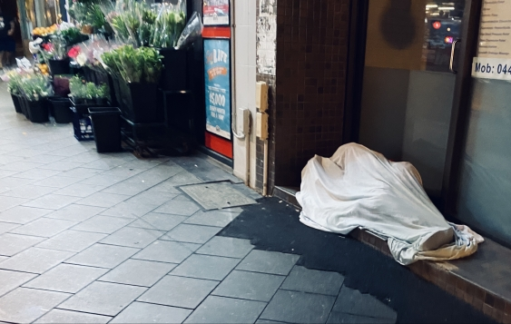 A man sleeps on a Sydney street at the start of the COVID-19 winter.