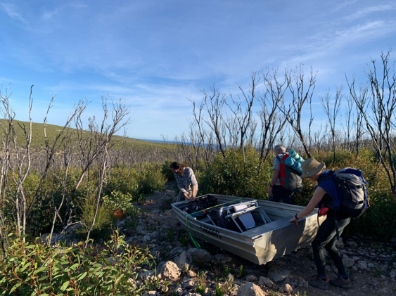 Researchers hauling a boat overland to reach the platypus traps