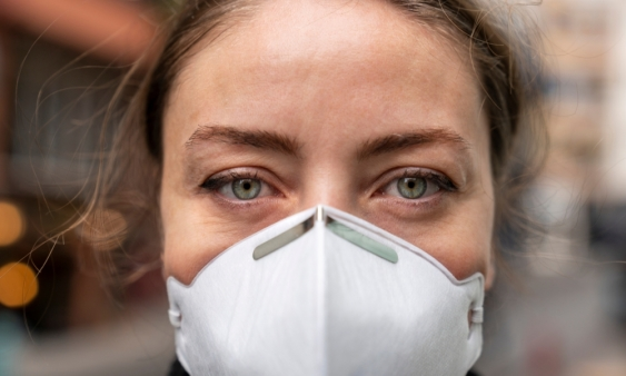 Young woman wears face mask looking into camera