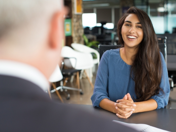 A young woman smiling confidently during job interview.