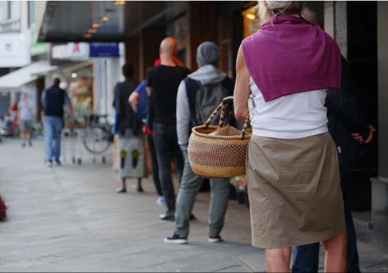 People standing a metre from each other outside of a shop with their backs turned from the photograph. A woman holding her wicker basket is the focus.