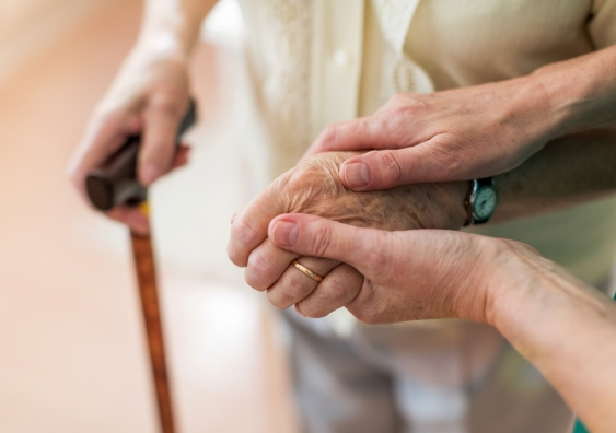 A nurse holding hands with an elderly person.