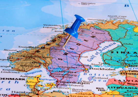 Map of Sweden and surrounding countries with blue pushpin stuck to Sweden.