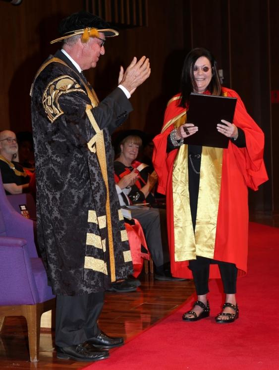 Gene Sherman receives her degree from Chancellor David Gonski