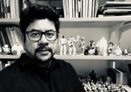 Dr Eduardo Benitez Sandoval sitting in front of shelves of robots, figurines and books