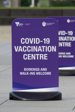 """Outdoor sign saying """"Covid-19 Vaccination Centre - Bookings and walk-ins welcome"""""""