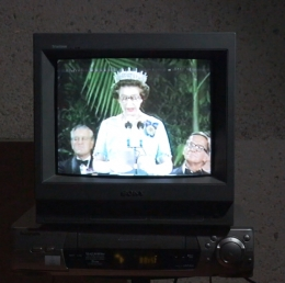 A television screen with an image of Queen Elizabeth II at the NGA opening