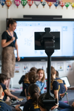 Telepresence robot surrounded by other students as teacher gives lesson