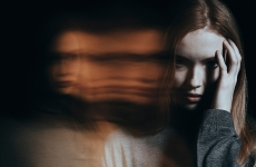 Young woman with hand up to face amid distorted reflections
