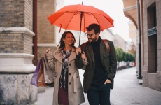 Man and woman holding shopping bags walk under an umbrella