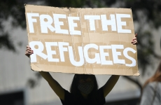 a street protester holds a sign that says free the refugees