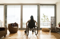 a woman in a wheelchair sits looking at a window filled with bright light