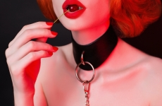 a woman wearing a leather collar and red lipstick holds a red cherry to her lips
