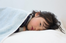 a young child lies on a pillow looking sad