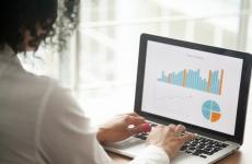Businesswoman analysing statistics on a laptop screen.