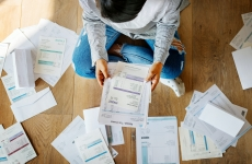A person sitting on the floor surrounded by tax receipts