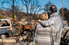 Couple stand at the ruins of their home after bushfire