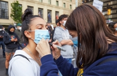 Female protestor writing 'I cant breathe' on fellow protestor's face mask