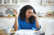woman at kitchen table looking exhausted