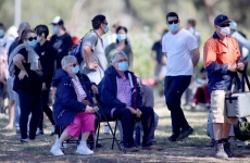 people wearing facemasks queueing for coronavirus tests