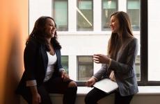 Two business women sitting near black full-glass panel window