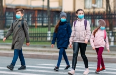 primary school-aged children walk across a zebra crossing wearing face masks