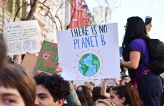 protesters hold a sign up saying there is no planet b