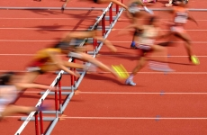 Runners on an athletics track jumping hurdles