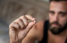 Man holding an ecstasy pill. Focus on the pill