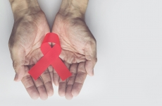 Man holding red aids ribbon, HIV/AIDS