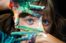 a young woman stares at camera through her fingers which are covered in colourful paint