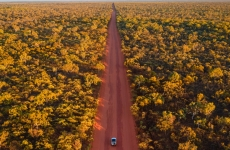 A car driving through the outback.