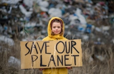 A child holding a poster on landfill with 'save our planet' written on it.