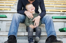 A man bending over and holding a laughing child