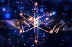 Artwork showing two hands about to touch behind a star shape of electron orbits