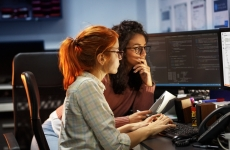 Two female software programmers looking at computer screens.