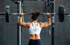 A strong-looking woman lifting weights in a gym