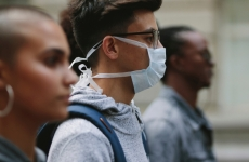 Three young adults one wears a protective face mask