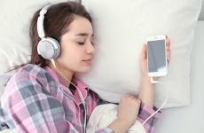 woman sleeping in bed while listening to music through headphones