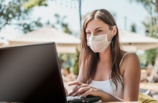 Woman wears face mask while sitting at a table by the beach with her laptop