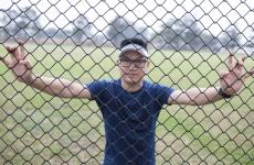Refugee Zaki Haidari behind a wire fence