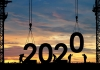 Silhouette of construction workers lowering giant numbers of 2020 into place