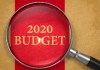 Magnifying glass over words 2020 budget.