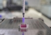 A syringe in a 3D-printer extruding ink into a special gel bath.