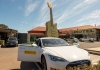 A Tesla car with UNSW emblem in front of The Big Golden Guitar, Tamworth