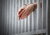A pair of handcuffed hands poking through bars of a jail cell