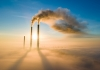 Waste gas is shown escaping two industrial chimneys against a blue sky background and surrounded by fog