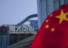 The Evergrande logo seen at the top of a building with the Chinese flag in the foreground