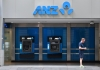 a man walks past anz automatic tellers in a wall